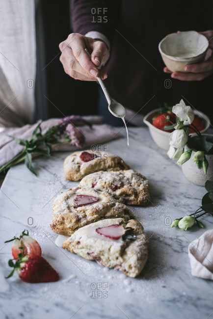 Unrecognizable person adding sweet cream sauce to tasty strawberry scones while cooking in kitchen
