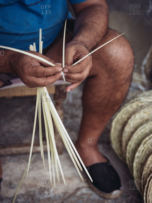 Unrecognizable adult man preparing dried palm fiber for weaving while sitting in shabby workshop