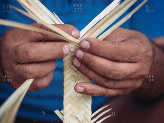 Close-up hands of anonymous craftsman using hook to weave dried palm leaves fiber while working in workshop