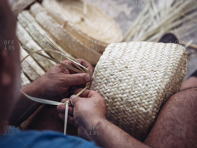 Hands of anonymous artisan showing lovely basket with floral ornament braided from dried palm fiber