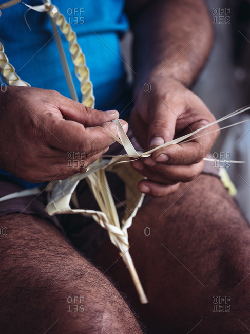 Close-up hands of anonymous craftsman weaving dried palm leaves fiber while working in workshop