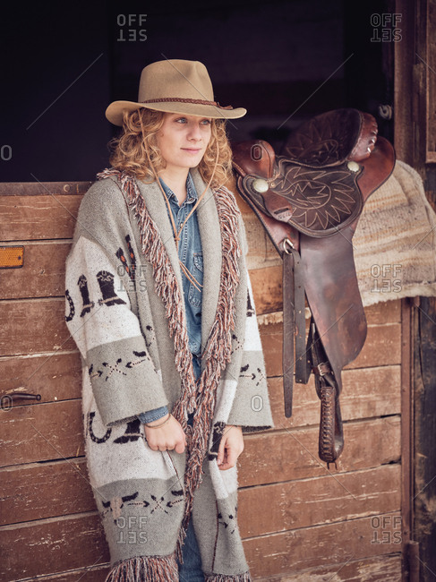 Beautiful cowgirl looking away while leaning on wooden stable wall near leather saddle on ranch