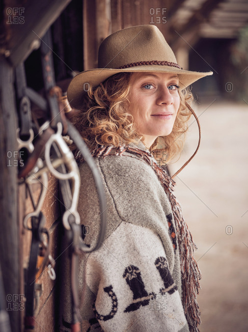 Beautiful cowgirl looking at camera on wooden stable wall near leather saddle on ranch