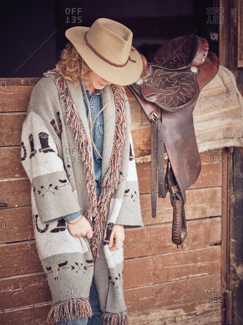 Beautiful cowgirl looking down while leaning on wooden stable wall near leather saddle on ranch