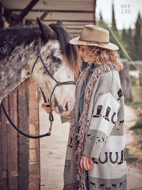 Cheerful cowgirl interacting with horse