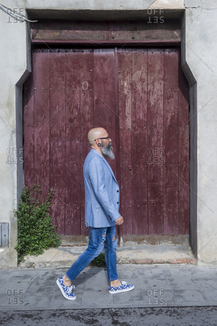 Side view of a mature trendy bearded hipster walking against a red vintage door outdoors