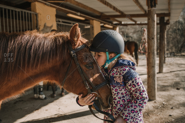 Cute little girl in helmet kissing a white horse while standing near stalls in stable during horseback riding lesson on ranch