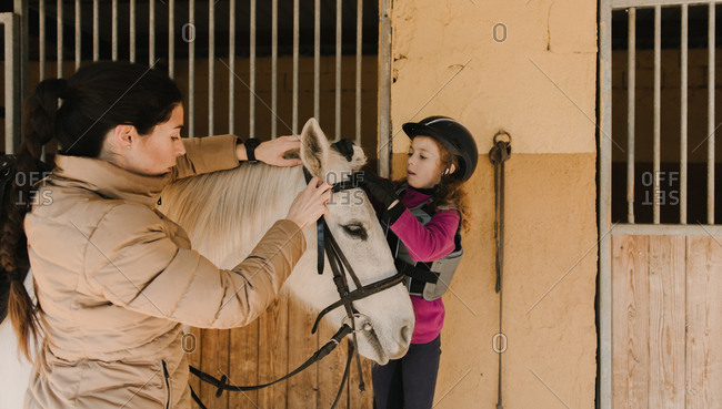 Pretty young female and cute little girl in helmet putting bridle on white horse while standing near stalls in stable during horseback riding lesson on ranch