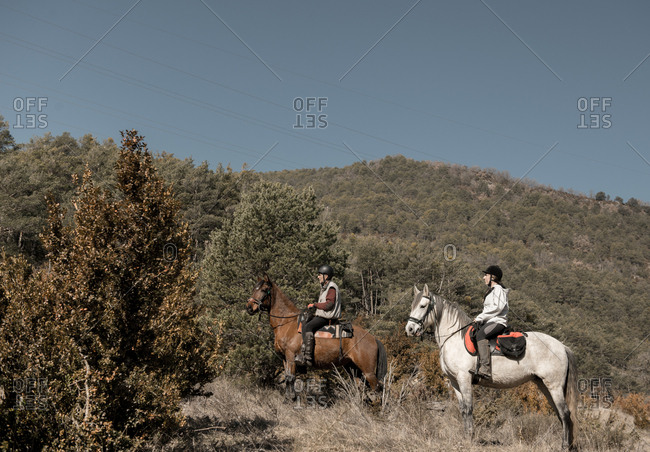 People riding horses in calm creek on sunny day in amazing autumn countryside during lesson