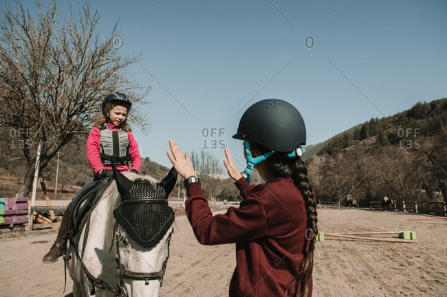 Young female in helmet teaching adorable little girl to ride horse during lesson on sunny autumn day on ranch