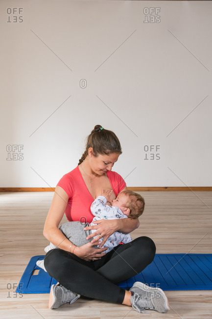 Beautiful woman in sportswear feeding cute baby with breast while sitting on floor in gym