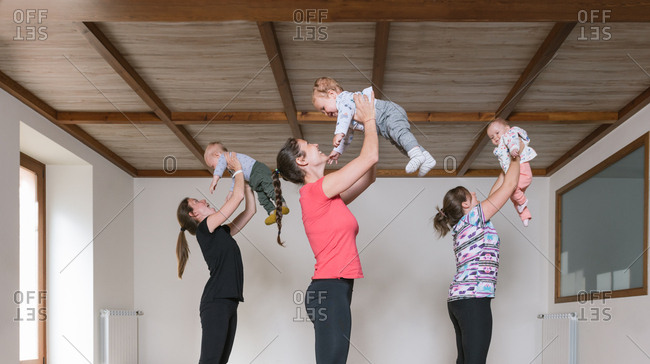 Side view of women in sportswear lifting cute babies over heads while exercising in modern gym together
