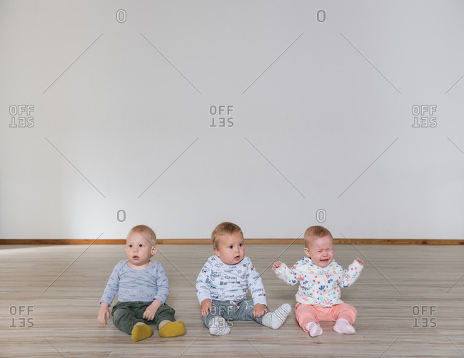 Three adorable babies crying and looking around while sitting on floor in gym