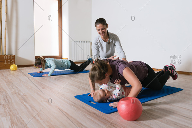 Friendly female trainer smiling and helping woman in sportswear perform push ups over cute baby during fitness workout in gym