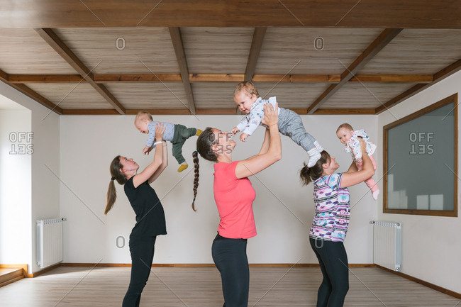 Mothers lifting babies in gym