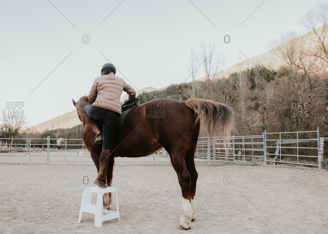 Back view of female in helmet mounting on obedient horse in enclosure on ranch
