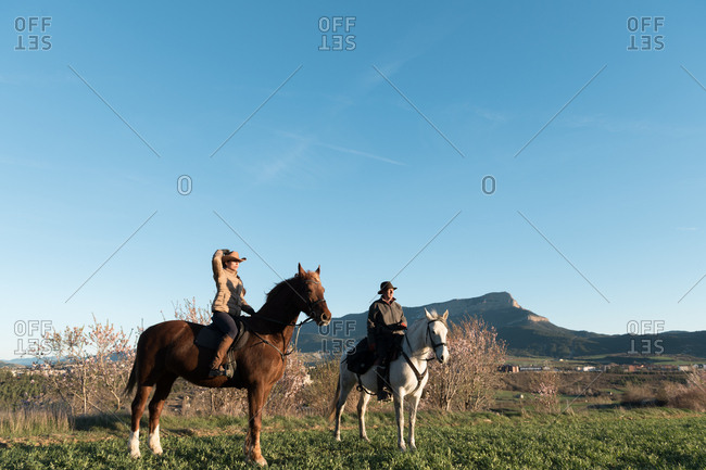 Man and woman riding horses on ranch