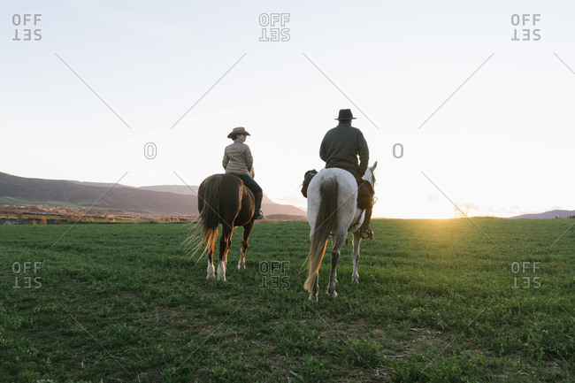 Back view of man and woman riding horses against sunset sky on ranch