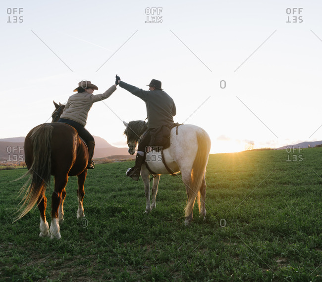 Back view of man and woman riding horses and giving high five to each other against sunset sky on ranch