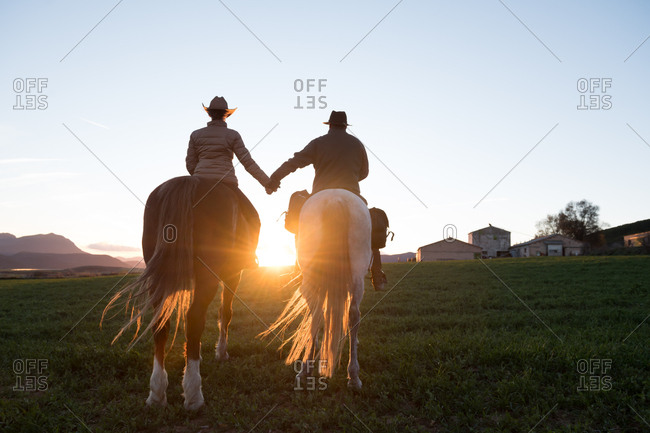Back view of man and woman riding horses and holding hands against sunset sky on ranch