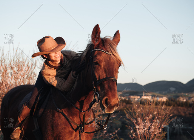 Woman riding horse against sunset sky on ranch
