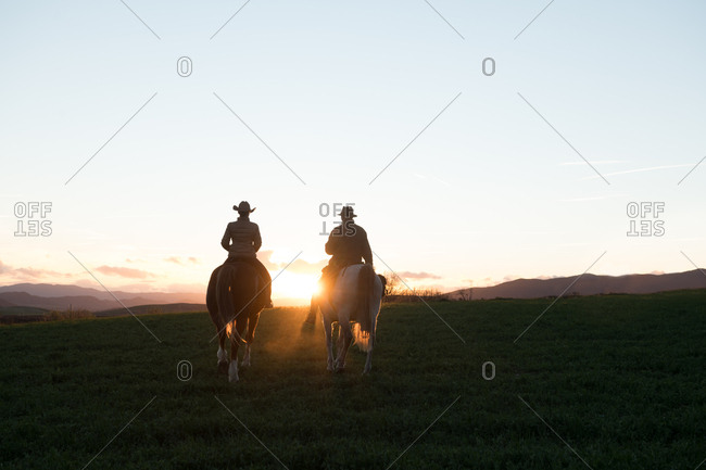 Man and woman riding horses against sunset sky on ranch