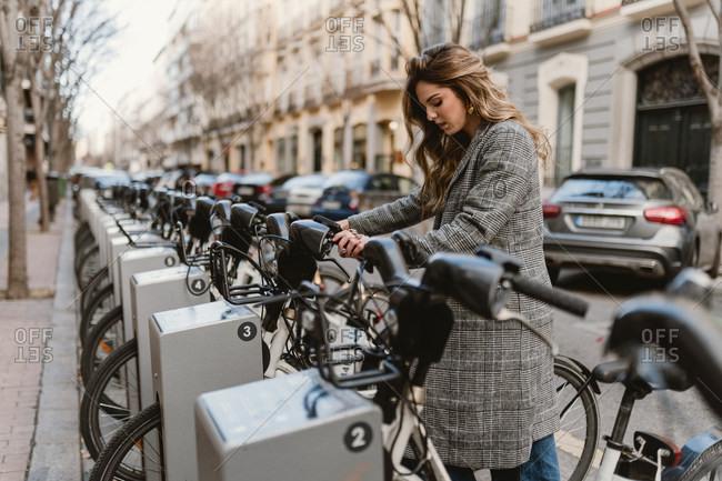 Lady choosing rental bicycle on parking lot