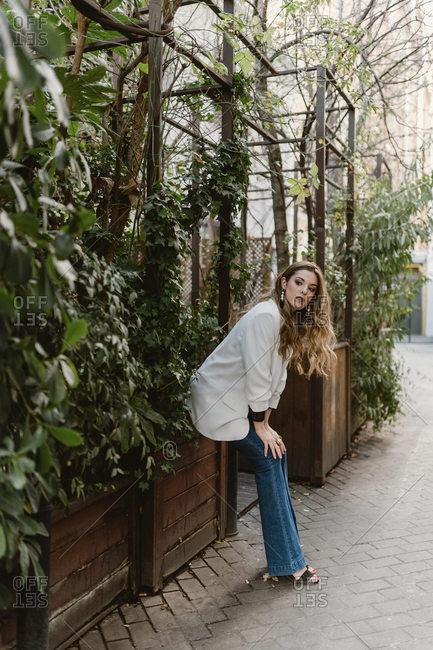 Woman sitting on planter in garden