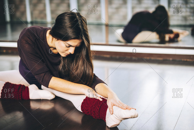 Girl practicing ballet and flexing muscles sitting on studio floor.