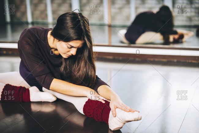 Girl practicing ballet and flexing muscles sitting on studio floor.