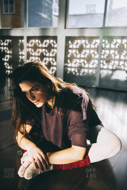 Young beautiful woman bending forward stretching legs while sitting on studio in sunlight.