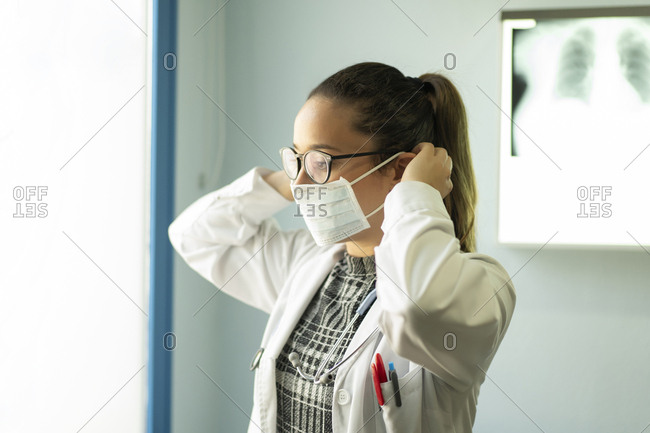 Side view of young female doctor in uniform and medical mask in room with x-ray film on wall