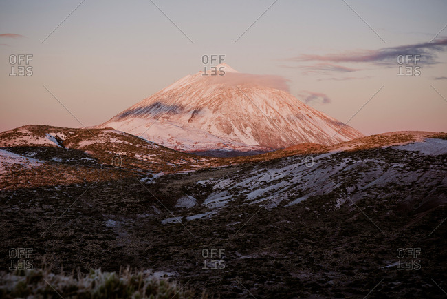 Majestic view of white clouds and wonderful snowy mountain peak against blue sky on Canary Islands, Spain