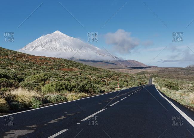 Asphalt countryside road going through grassy terrain near magnificent snowy mountain peak on sunny day on Canary Islands, Spain