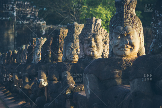 Row of weathered stone statues located near old oriental temple on sunny day