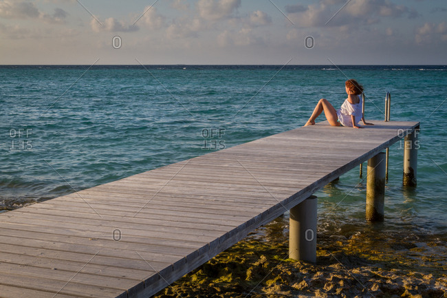Side view of pretty young female looking away while sitting on wooden pier near rippled sea water against cloudy evening sky in Maldives