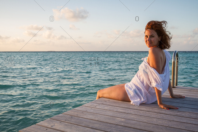 Side view of pretty young female smiling and looking at camera while sitting on wooden pier near rippled sea water against cloudy evening sky in Maldives