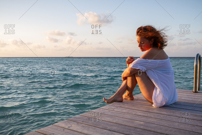 Side view of pretty young female looking down while sitting on wooden pier near rippled sea water against cloudy evening sky in Maldives