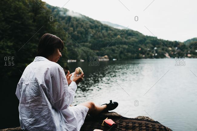 Woman eating hamburger near lake and mountains