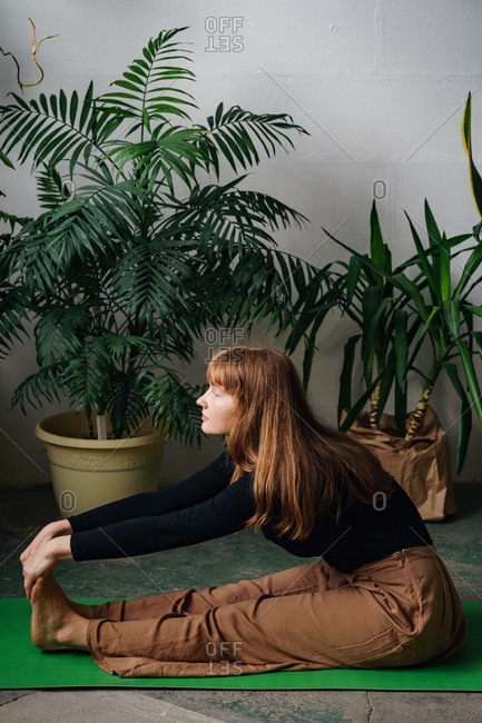 Red headed young woman stretching sitting on a green yoga mat surrounded by lots of house plants