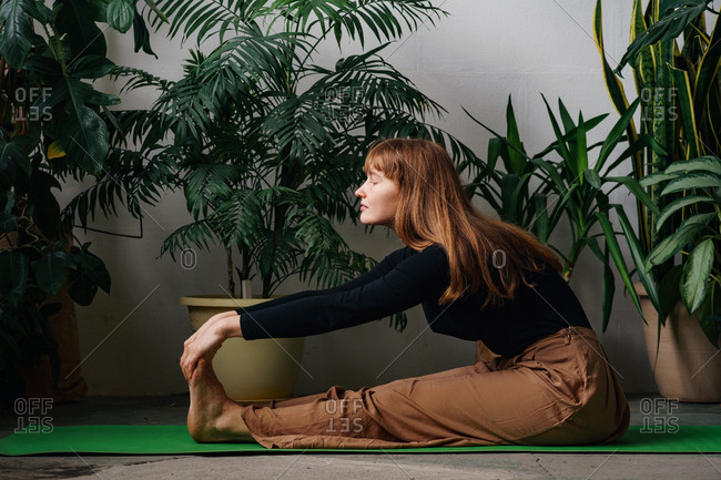 Young woman with red hair stretching sitting on a green yoga mat surrounded by many house plants