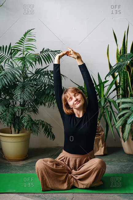 Redheaded young woman stretching on a green yoga mat surrounded by lots of house plants