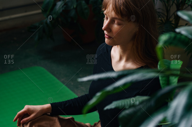 Profile of a young redheaded girl meditating in the room full of plants