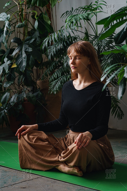 Young redheaded girl meditating in the room full of plants