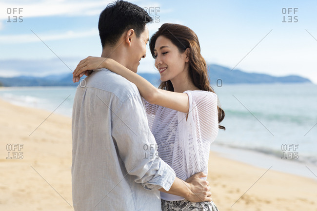 Happy young couple embracing on beach