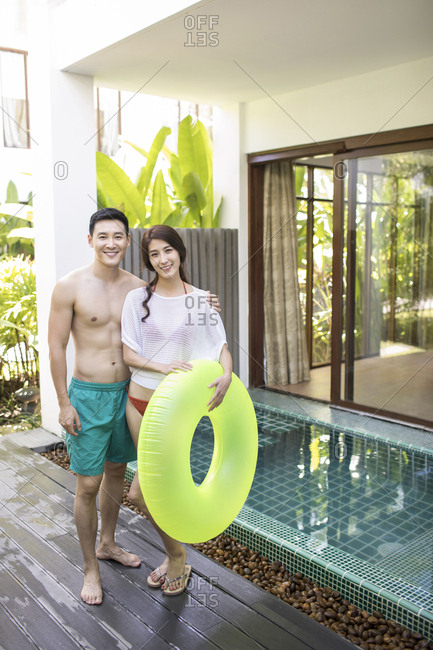 Happy young couple at poolside