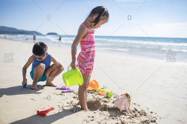 Children playing with sand on beach