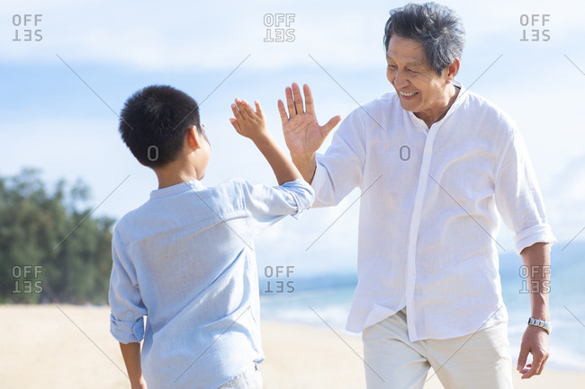 Grandfather and grandson doing high five on beach