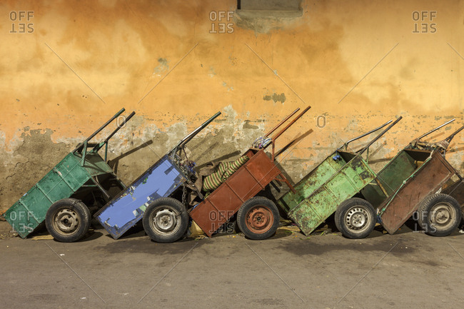 Row of carts against weathered wall