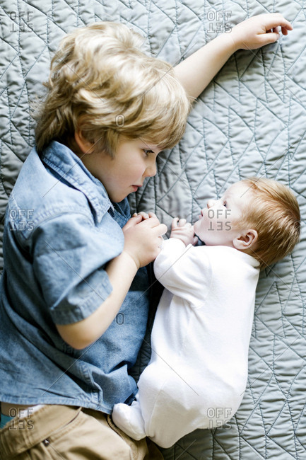 View directly above boy with his baby brother lying on bed